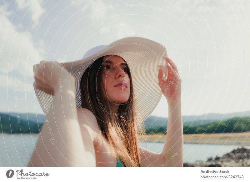 Junge Frau mit Hut ruht sich am Strand aus See ruhen Sommer jung verträumt wolkig Himmel Wasser Urlaub Wochenende Lifestyle Natur Landschaft Kopfbedeckung