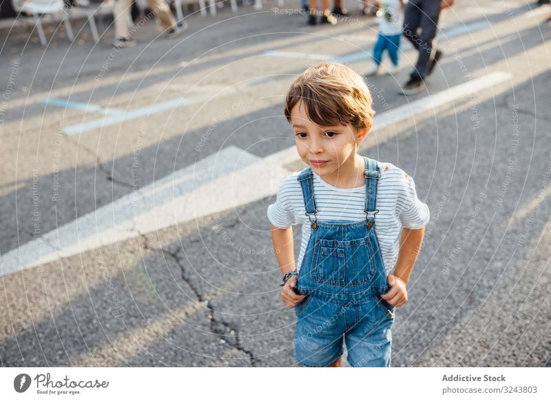 Kleiner Junge schaut auf der Straße weg Großstadt neugierig lässig wenig bezaubernd modern ruhen Hände an der Taille Asphalt urban Kind Lifestyle