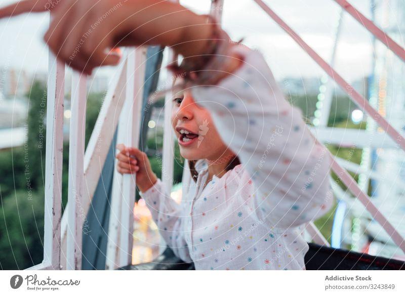 Fröhliches Mädchen fährt Riesenrad mit Eltern Mitfahrgelegenheit aufgeregt Mutter Spaß Herbst Vergnügungspark Lachen Kind Tochter Entertainment Beobachtung Höhe