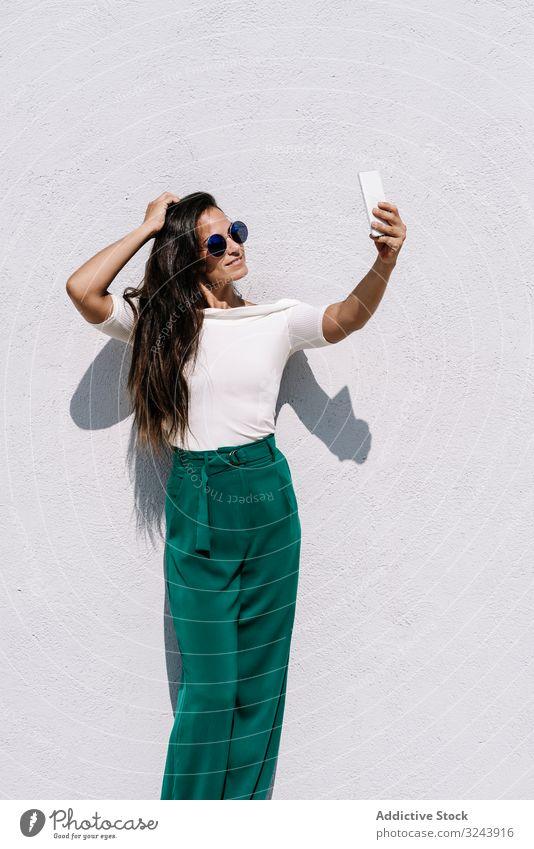 Attraktive junge Frau in trendigem Outfit, die vor hellem Hintergrund für Selfie posiert trendy Smartphone Stil Model urban lässig Lifestyle posierend