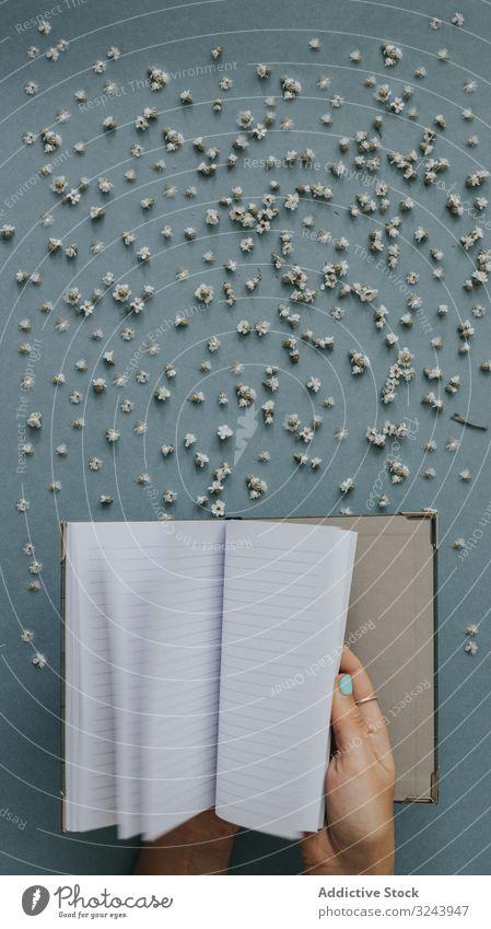 Person blättert leeres Notizbuch auf blauem Hintergrund mit winzigen Blumen Nachricht Notebook blanko Papier Streuung Hinweis Design Fliege Konzept Flip