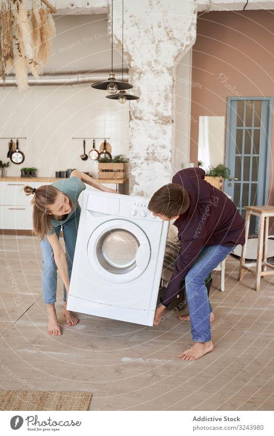 Enthusiastisches Paar trägt Waschmaschine in neue Küche bewegend einrichten Appartement Vorrichtung heimwärts führen heimisch heiter Versand Anwesen
