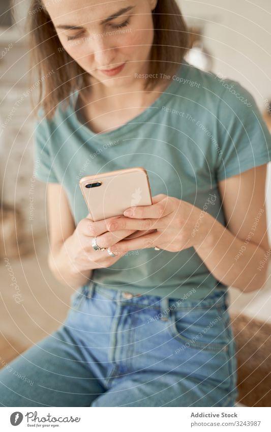 Entspannte Frauen sitzen an der Waschmaschine und surfen auf dem Smartphone Browsen heimwärts Haus heimisch benutzend Raumpfleger soziale Netzwerke räkeln