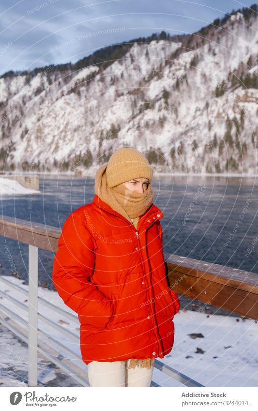 Frau genießt Landschaft mit Fluss und schneebedeckten Bergen Berge u. Gebirge Winter Bank Sibirien verschneite Natur Felsen Hügel Zaun kalt Flussufer malerisch