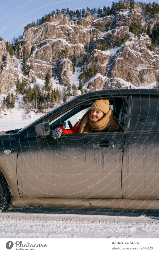 Frau lehnt sich aus dem Autofenster im verschneiten Tal PKW Fenster Berge u. Gebirge Winter Sibirien Autoreise Glück genießen Lächeln Natur Landschaft Felsen
