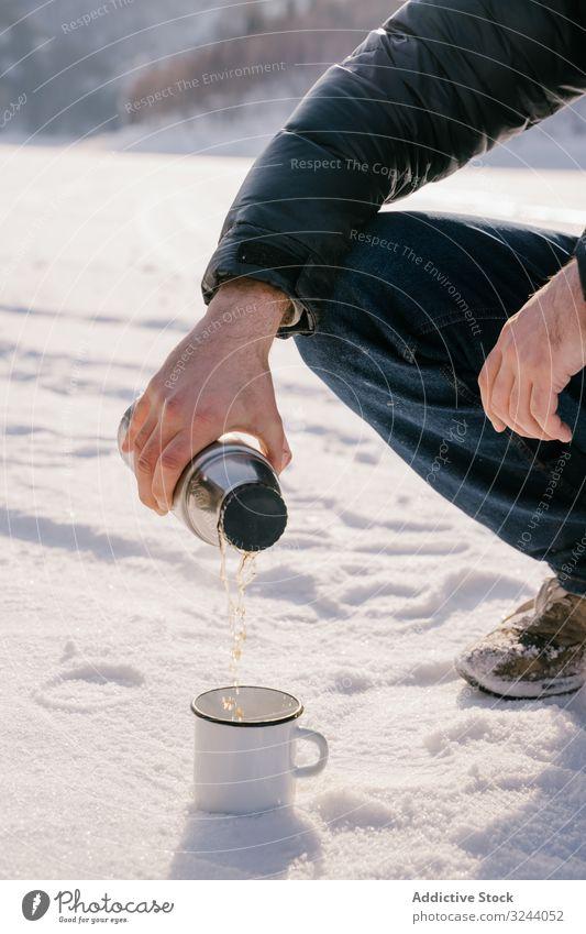 Mann gießt am Wintertag Tee aus Thermosflasche Thermoskanne Schnee eingießen Sibirien Natur kalt Aufwärmen Russland männlich sitzen heiß Pause Flasche ruhen