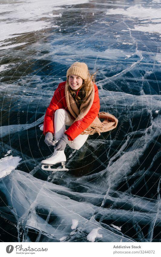 Frau sitzt auf gefrorenem Fluss und bindet sich die Schnürsenkel Schnee Stiefel das Binden der Schnürsenkel Schlittschuhe anmachend Winter Wandel & Veränderung
