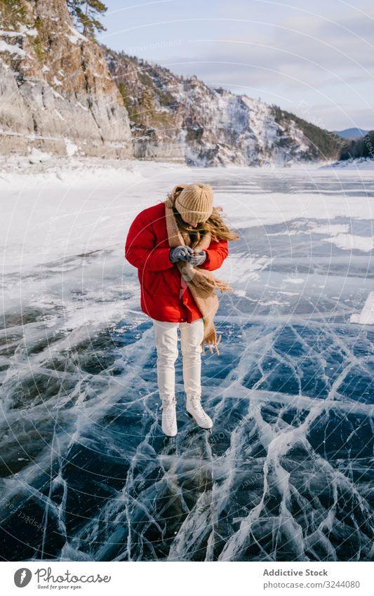 Frau in Schlittschuhen steht auf dem Eis und benutzt Telefon benutzend Schlittschuhlaufen Fluss Winter kalt Aktivität Smartphone Mobile Nachricht Anruf