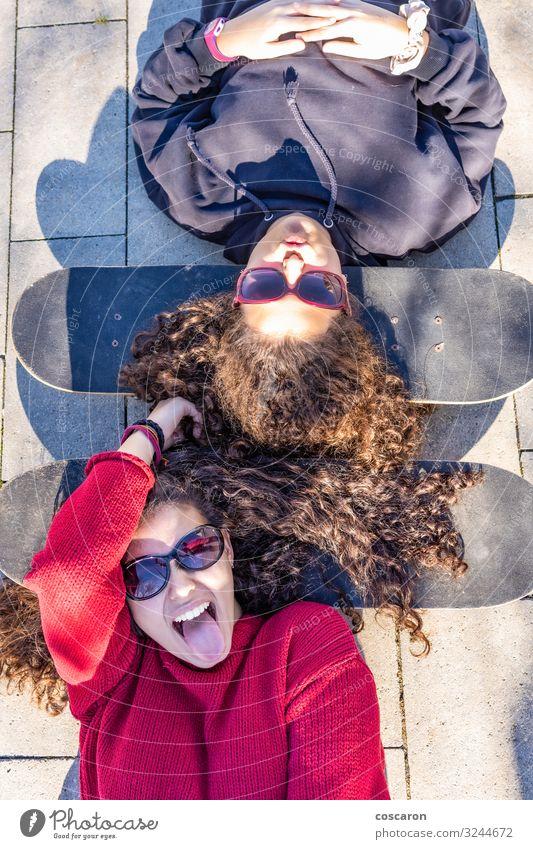 Zwei junge Skater, die mit den Köpfen auf ihren Boards ruhen. Lifestyle Stil Freude Glück Freizeit & Hobby Brettspiel Sommer Sport Mensch feminin Junge Frau