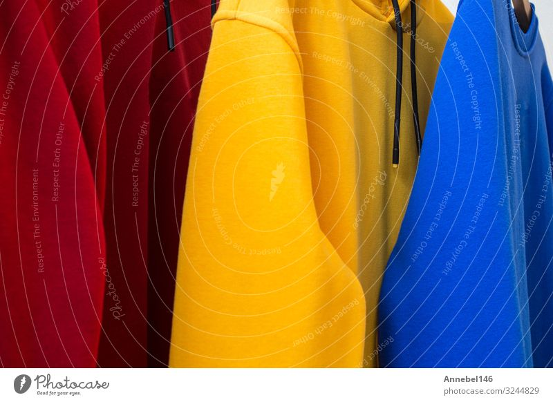 Bunte Kapuzenpullover auf Bügeln Nahaufnahme modernes Design Lifestyle kaufen Stil Frau Erwachsene Mann Mode Bekleidung Hemd Pullover Stoff Sammlung hängen hell