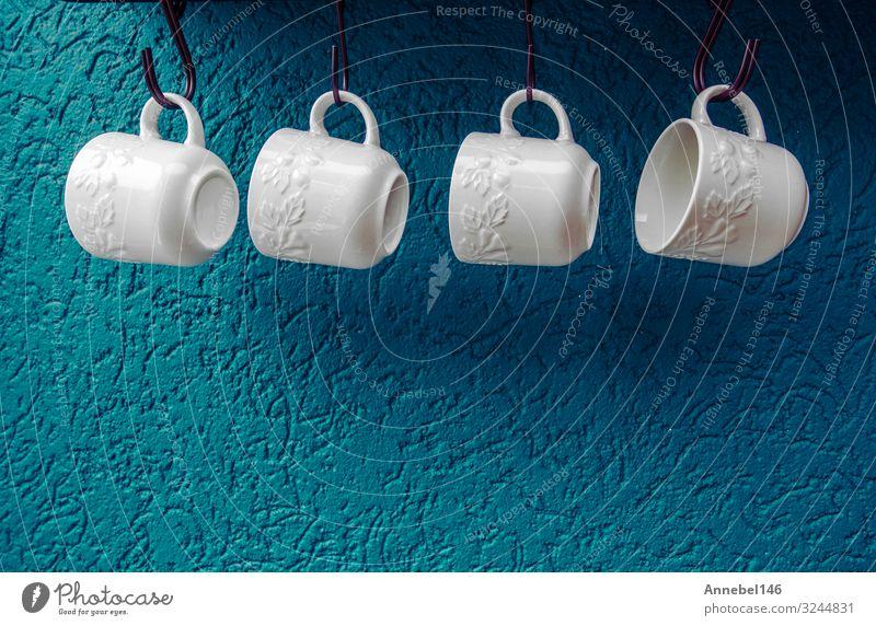 Kaffeetassen hängen an Haken der blauen Küchenwand. Frühstück Tee elegant Design Leben Restaurant Holz alt hell retro gelb grün rot weiß Farbe Becher Tasse