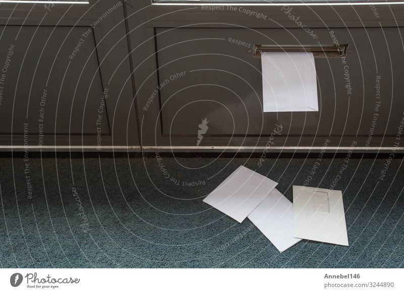 Auf dem Boden und im Türbriefkasten liegende Post Haus Zeitung Zeitschrift Fußmatte Briefkasten Papier Paket Holz Metall alt außergewöhnlich dunkel modern braun