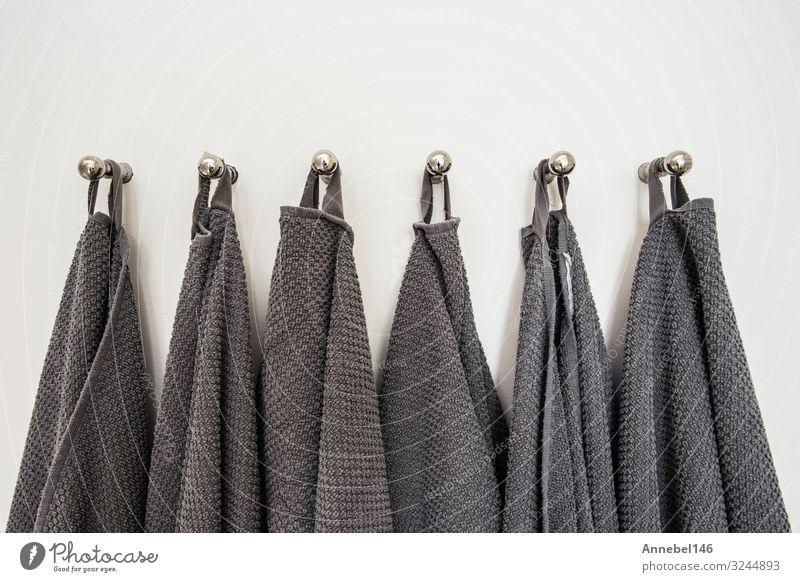 Graue Handtücher in einer Reihe hängend, auf Kleiderbügel vorbereitet. weiße Wand Spa Ferien & Urlaub & Reisen Haus Bad Stoff Metall Stahl Sauberkeit weich grau