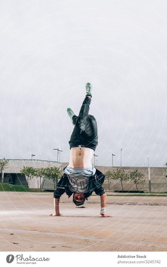 Geschickter Breakdancer mit Handstand in der Bewegung cool stylisch Kultur Streetstyle Lifestyle Hip-Hop flippig Stil Freestyle Spaß Leistung Sport Straße jung
