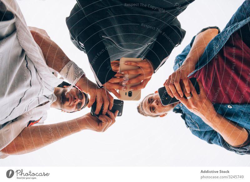 Elegante Teenager benutzen Smartphone im Freien Freunde benutzend Browsen Surfen zuschauend Mobile Telefon entwirft Gadgets soziale Netzwerke Hipster Schüler