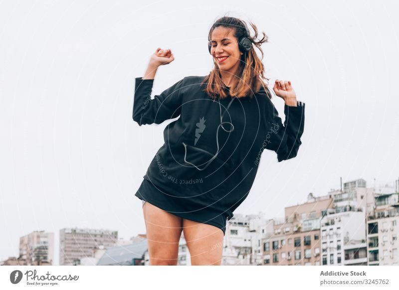 Zufriedene junge Frau in Freizeitkleidung tanzt mit Kopfhörern auf der Straße hören Musik Gerät Tanzen Erhöhung Hände Waffen Gesang Radio Rhythmus Lächeln