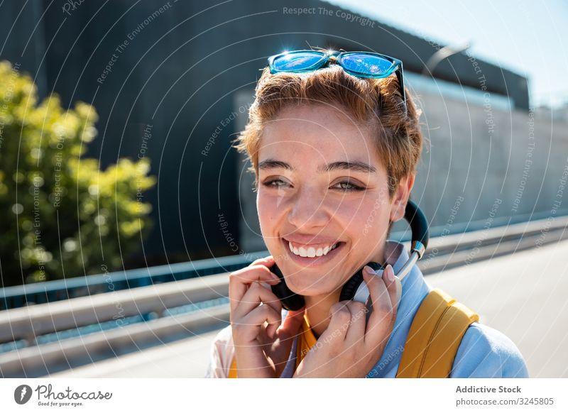 Verspielte trendige Frau auf der Straße bei Sonnenschein, die die Kamera mit den Händen bedeckt hell Lächeln spielerisch Sonnenbrille tausendjährig Kopfhörer