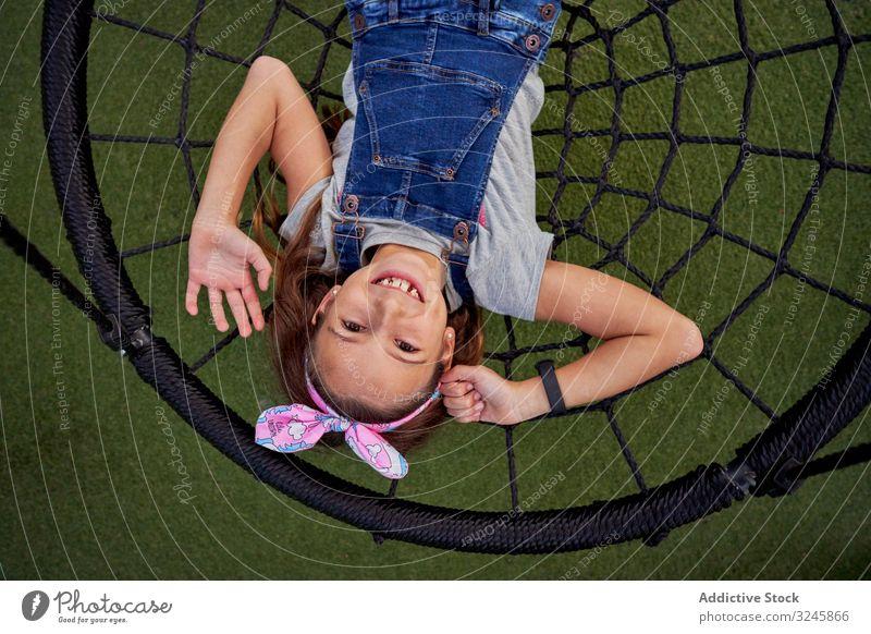 Glückliches Mädchen hat Spaß beim Korbschwingen pendeln spielen sorgenfrei Teenager Overall Spinnennetz Lügen Lächeln Spielplatz genießen aufgeregt spielerisch
