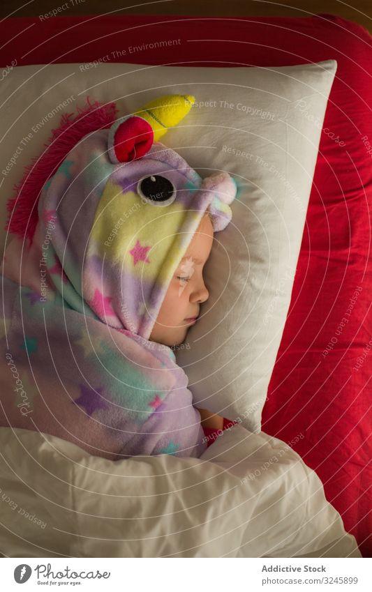 Mädchen im Einhornpyjama schläft im Bett Kind schlafen Pyjama kigurumi Decke rot weiß träumen Lügen niedlich wenig Kindheit Nacht Schlafenszeit heimwärts