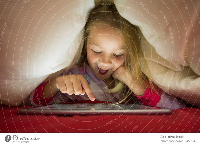 Mädchen benutzt Tablette unter einer Decke Bett Tierhaut benutzend zuschauend Spielen Schlafenszeit Pyjama Lügen Kind Glück Spaß positiv genießen rot weiß