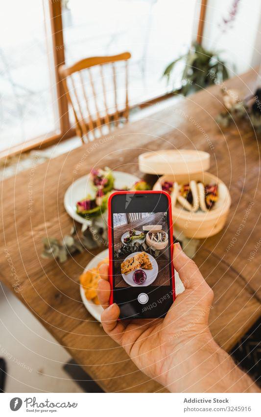 Fotograf beim Fotografieren von Lebensmitteln mit Smartphone fotografierend Food-Fotografie Bild Hand Mobile Funktelefon Telefon Tisch Mahlzeit Teller Speise