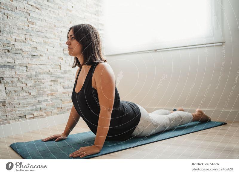 Frau meditiert zu Hause Meditation Yoga heimwärts Pose Unterlage praktizieren Morgen Raum Erholung jung brünett Wellness passen Gesundheit Windstille Zen