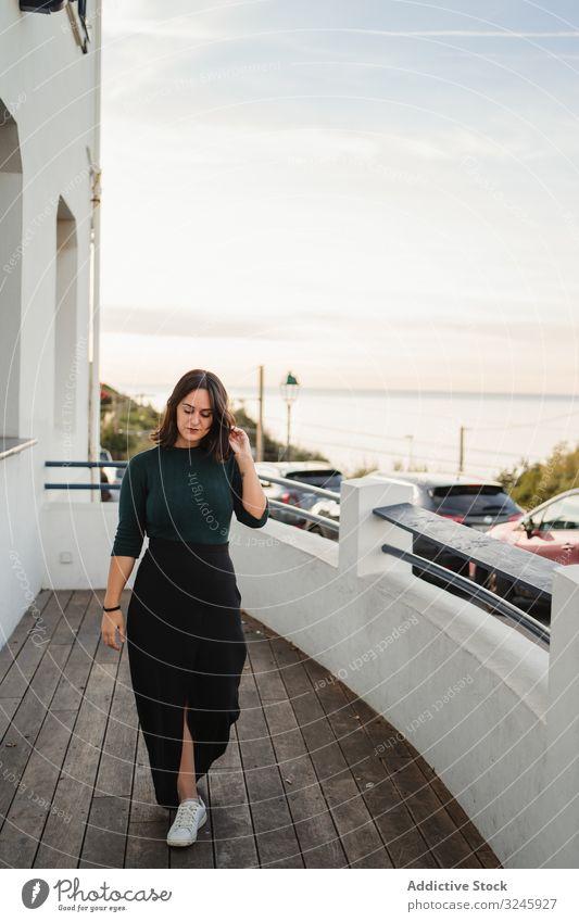 Nachdenkliche Frau geht auf Balkon Haus Küste Flussufer Seeküste nachdenklich besinnlich laufen lässig jung Windstille heimwärts hölzern Geländer Gebäude ruhen