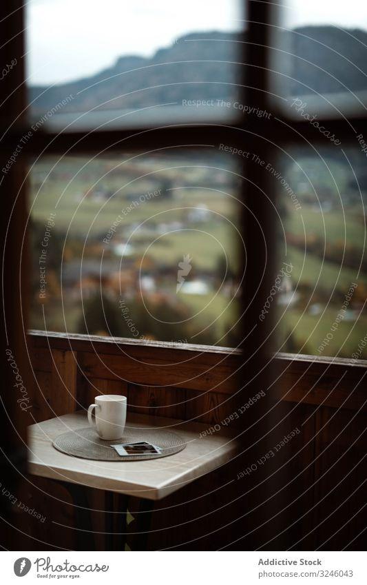 Kleiner Tisch mit einer Tasse Kaffee und Fotos auf der Terrasse an einem bewölkten Morgen Natur Berge u. Gebirge Tee Getränk Gedächtnis ländlich modern