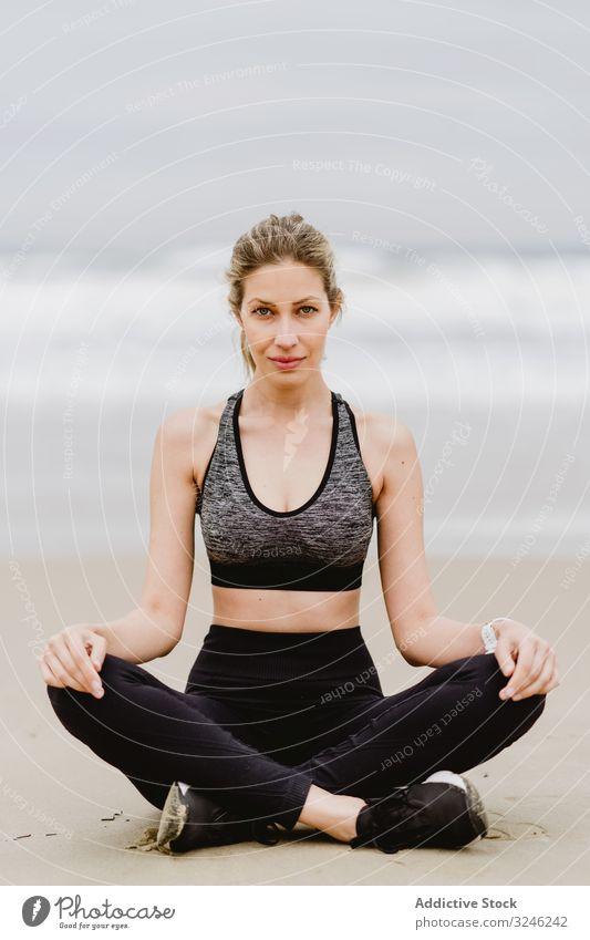 Am Strand meditierende Frau Yoga üben MEER Meer Übung Gleichgewicht Training jung Athlet aktiv Windstille Ruhe Sportbekleidung Körper Fitness Gesundheit