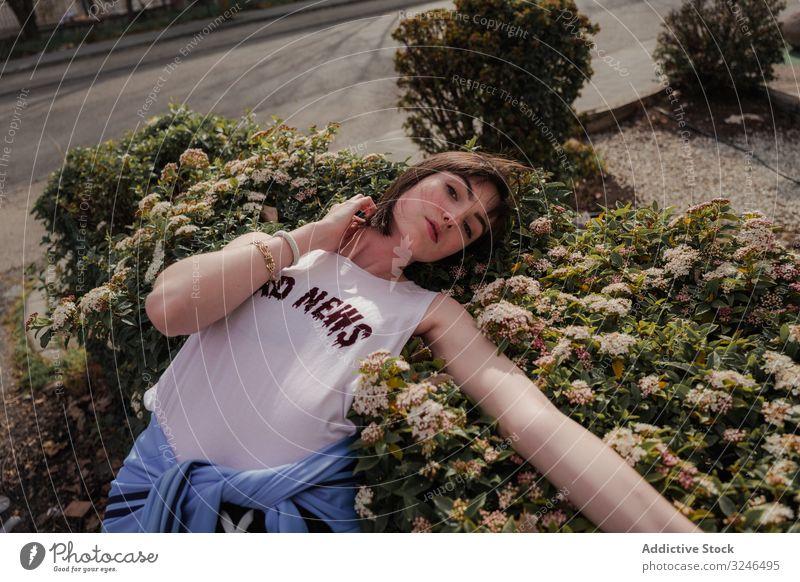 Junge Dame in trendigem Freizeit-Outfit am Strauch mit Blumen in der Stadtstraße Teenager modisch trendy stylisch lässig Lehnen Sommer emotionslos blumige
