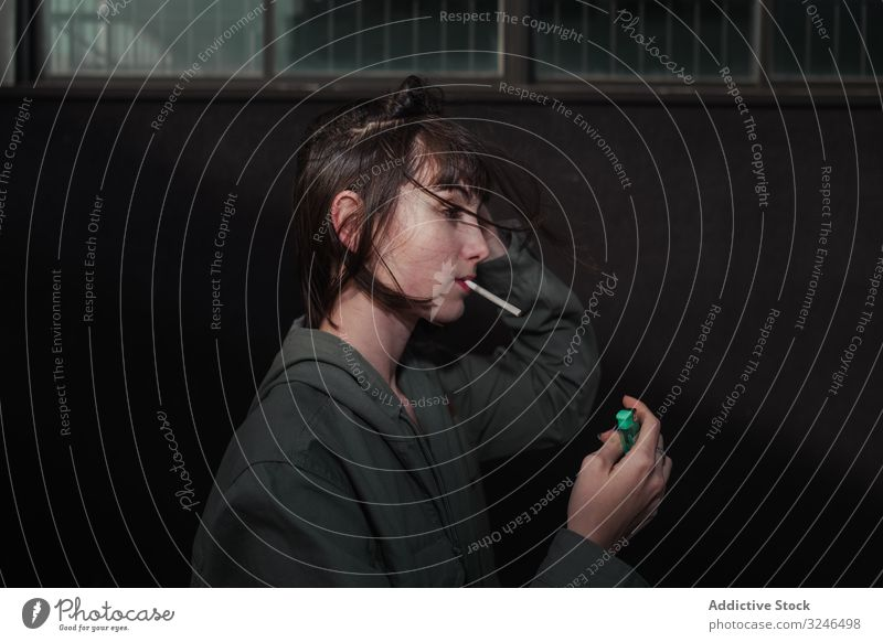 Weiblicher Teenager in Freizeitkleidung raucht Zigarette auf der Straße in der Stadt Rauchen aufleuchten Beteiligung Liter lässig Bekleidung anhaben Jacke