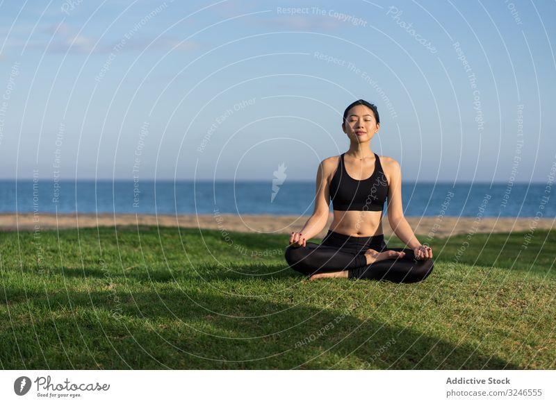 Am Strand meditierende Frau Yoga üben Gras grün MEER Meer stehen Übung Gleichgewicht Training jung Athlet aktiv Windstille Ruhe Sportbekleidung Körper Fitness
