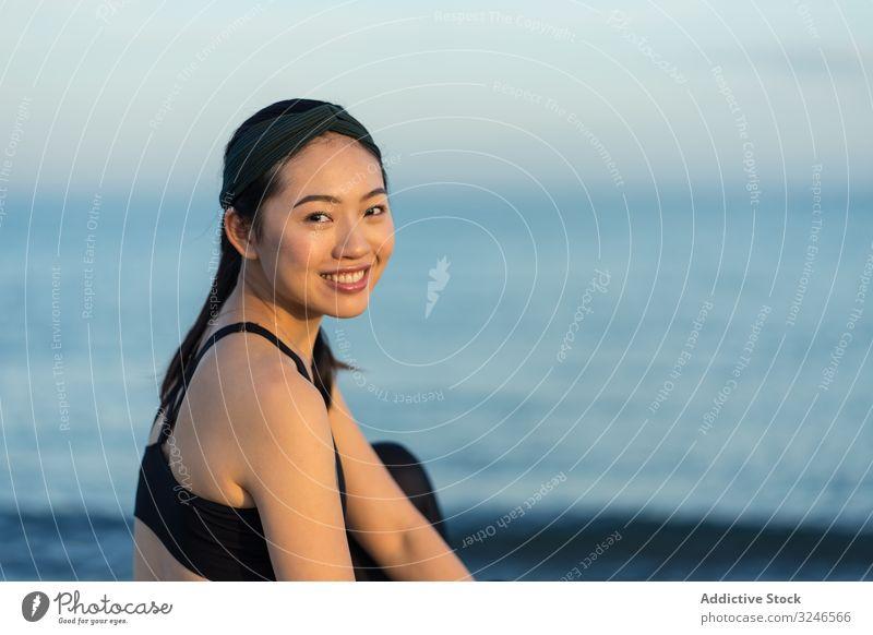 Sportliche Frau sitzt am Strand Sitzen sportlich MEER Meer sitzen jung Sportbekleidung sich[Akk] entspannen ruhen genießen asiatisch ethnisch Windstille Ruhe