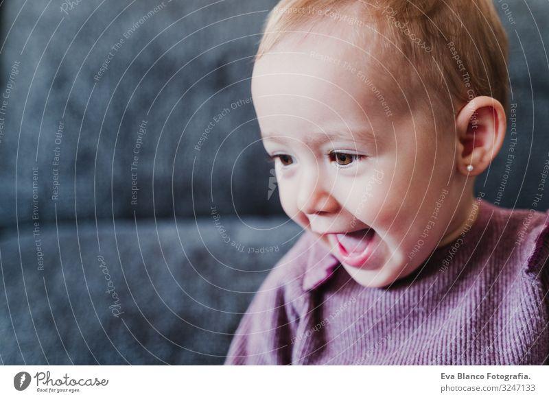 schönes kleines Mädchen, das zu Hause lacht und auf dem Sofa sitzt. Lifestyle Freude Leben Freizeit & Hobby Spielen Wohnung feminin Baby Kindheit 1 Mensch