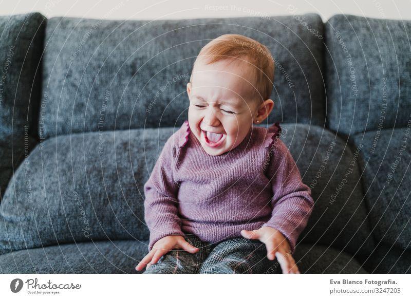 schönes kleines Mädchen, das zu Hause lacht und auf dem Sofa sitzt. Lifestyle Freude Glück Leben Freizeit & Hobby Spielen Wohnung Baby Frau Erwachsene Kindheit