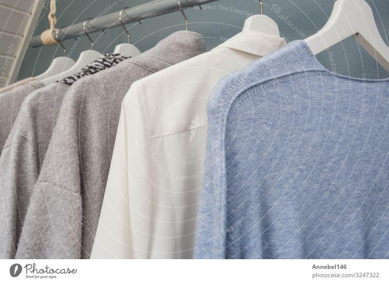 Die Kleidung hängt an einem Kleiderständer, weiß, grau und blau, kaufen Stil Sommer Business Frau Erwachsene Mode Bekleidung T-Shirt Hemd Jacke Stoff Sammlung
