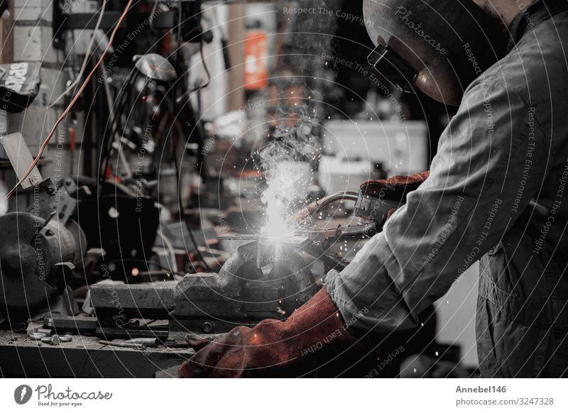 Schweißer schweißt Metallteil in der Garage. mit Schutzmaske, Arbeit & Erwerbstätigkeit Beruf Arbeitsplatz Fabrik Industrie Werkzeug Technik & Technologie Mann