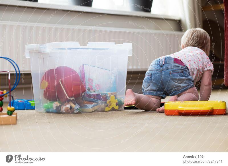 Baby spielt allein mit Spielzeug auf einem Teppich auf dem Boden zu Hause Lifestyle Freude Glück Erholung Freizeit & Hobby Spielen Wohnzimmer Kind Mensch