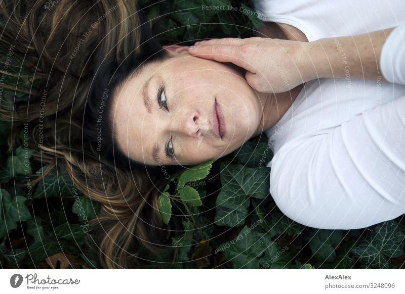 Portrait einer jungen Frau im Wald auf Efeu Natur Jugendliche Junge Frau Pflanze schön Erholung ruhig Gesicht Erwachsene natürlich Stil Ausflug liegen