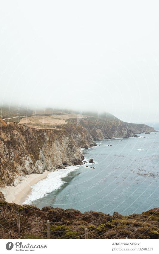 Blaue Wellen umspülen felsige Meeresküste bei strahlendem Sonnenschein Meeresufer Wasser Himmel Natur MEER Landschaft Küste Strand Felsen Ufer reisen Tourismus