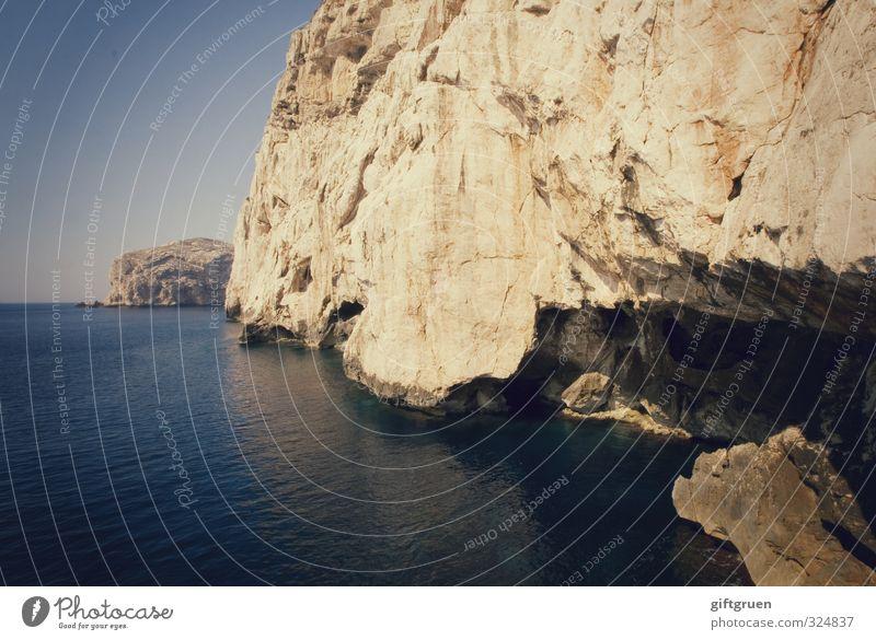 zahn der zeit Umwelt Natur Landschaft Urelemente Erde Wasser Himmel Wolkenloser Himmel Horizont Schönes Wetter Felsen Küste Meer groß blau Höhle ausgehöhlt
