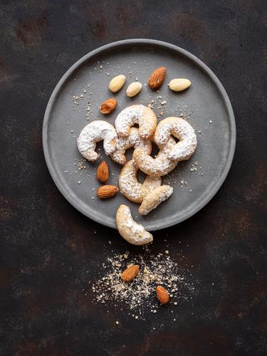 Vanillekipferl mit Mandeln auf einem grauen Teller Lebensmittel Teigwaren Backwaren Keks Österreich Weihnachten & Advent rustikal Tisch genießen alt Duft süß
