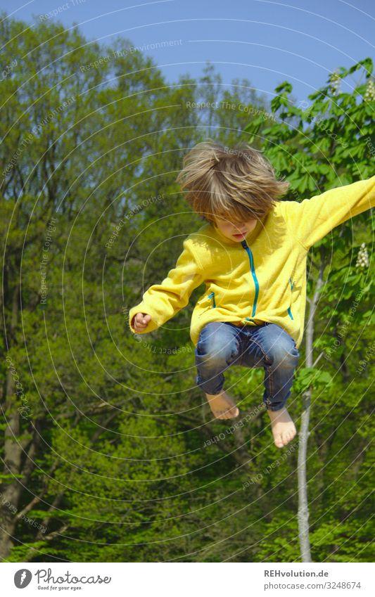 kind springt hoch springen sprung Dynamisch Bewegung aktiv sportlich Sport Spielen Spielplatz gelb grün Bäume Barfuß spass Trampolin Junge Jacke Sommer hüpfen