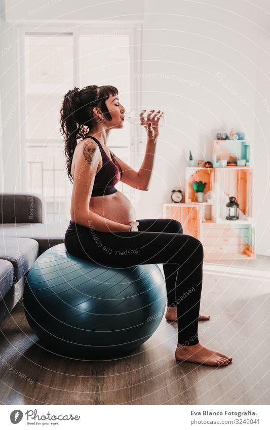 junge schwangere Frau zu Hause, die auf einem Pilates-Ball sitzt und Wasser trinkt. gesunde Lebensweise Yoga heimwärts Sport Gesundheit Lifestyle Jugendliche