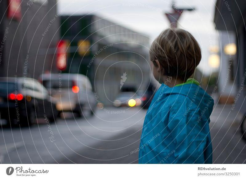 Junge steht an der Straße trüb schlechtes Wetter lichter Licht Personenverkehr Verkehrsmittel Stadtzentrum Fahrzeug Straßenkreuzung Farbfoto Fußgänger