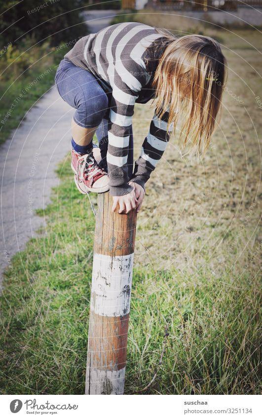 kletterin (2) Kind Mädchen jungennhaft Klettern Spielen gewagt Pfosten Holzpfahl Zaunpfahl festhalten Außenaufnahme Fußweg Natur toben Kindheit Geschicklichkeit
