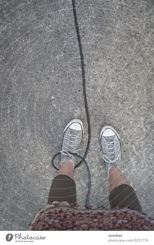 den fuß in der schlinge haben Füße Beine Frau stehen Kabel Schlaufe gefangen gefesselt Freiheitsberaubung laufen angekettet Straße Asphalt Vorsicht Gefahr