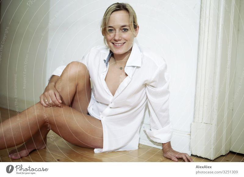 Junge Frau sitzt auf Dielenboden und lächelt Stil Freude schön Leben Wohnung Jugendliche Erwachsene Gesicht Beine 30-45 Jahre Altbauwohnung Hemd Barfuß blond