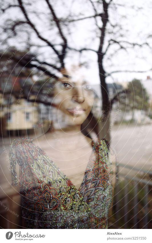 Portrait einer Frau hinter einer Fensterscheibe Stil schön harmonisch Wohnung Stadt Junge Frau Jugendliche 18-30 Jahre Erwachsene Schönes Wetter Baum Straße