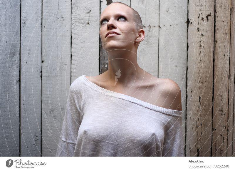 Frau schaut zum Oberlicht vor Bretterwand Stil schön Dachboden Holzwand Junge Frau Jugendliche 18-30 Jahre Erwachsene T-Shirt Brustwarze Glatze Blick ästhetisch
